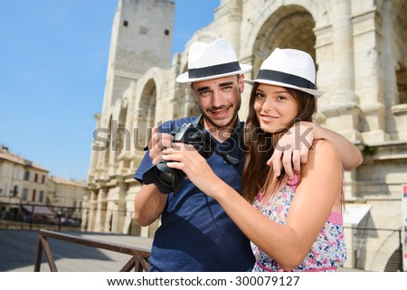 happy young couple tourist playing with a camera in front of a famous monument