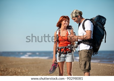 happy, young couple walking together on a deserted beach, wearing backpacks, talking