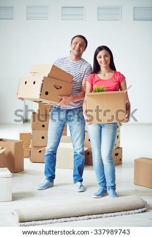 Happy young couple with moving boxes in their new house