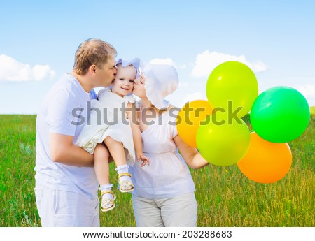 happy young family with balloons outdoor on a summer day