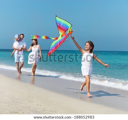 Happy young family with flying a kite on the beach