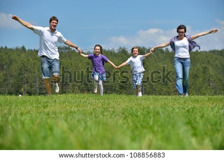 happy young family with their kids have fun and relax outdoors in nature with blue sky in background