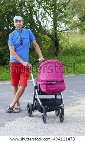 Happy young father with a stroller outdoors