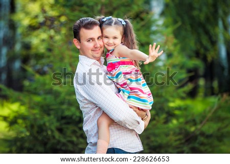 Happy young father with little daughter outdoor