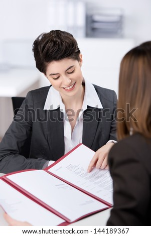 Happy young female candidate explaining her CV in job interview