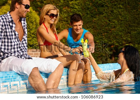 Happy young friends having drinks at swimming pool, smiling, enjoying holiday.