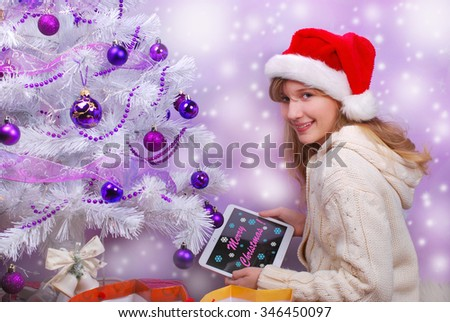 happy young girl sitting close to christmas tree and opening perfect christmas gift with tablet pc