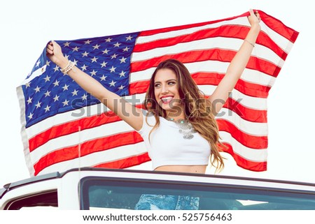 Happy Young Girl Standing In Convertible Car Looking Away Holding Waving American USA Flag For Independence Day. Selective Focus.