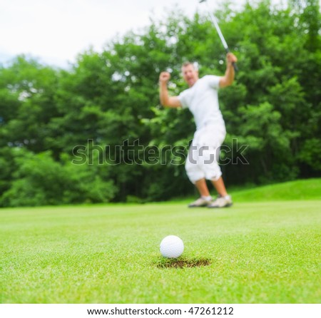 Happy young golfer after sending golf ball to the hole. Focus on ball.
