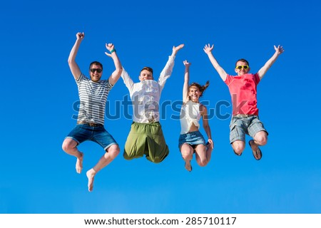 Happy young group of people jumping in the blue sky