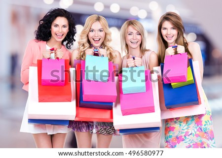 Happy young group of women with shopping bags after shopping in the big mall
