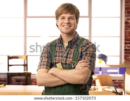Happy young handyman carpenter in workshop, smiling.