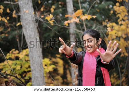 happy young indian girl enjoying autumn