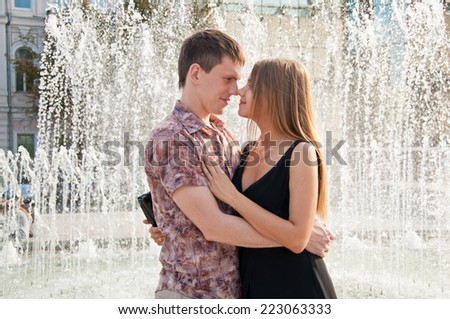 Happy young love couple standing near fountain