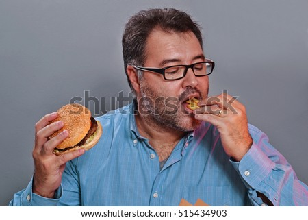 Happy young man eating fried potatoes and burger.