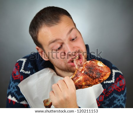 happy young man eating meat