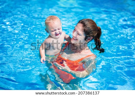 Happy young mother and her little son, adorable laughing baby boy having fun together in an outdoor swimming pool on a hot summer day during vacation in a tropical resort