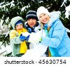happy young mother, father and their little son spending time outdoor in winter park - stock photo