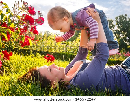 Happy young mother playing with little daughter in park