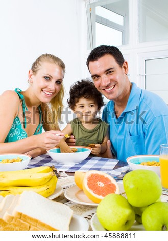 happy young parents and toddler boy at breakfast table