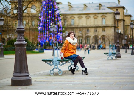 Happy young tourist in Paris on a winter day, main Parisian Christmas tree in the background