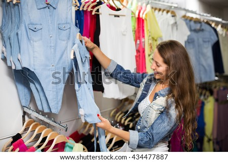 Happy young woman choosing cloths in shop
