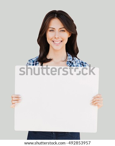 Happy young woman holding blank white banner isolated on gray background