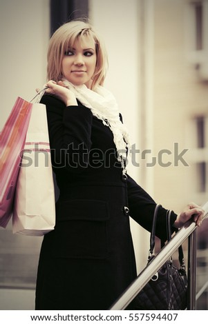 Happy young woman in black coat with shopping bags Stylish fashion model outdoor