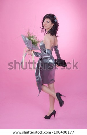 Happy young woman in evening dress with a bouquet, of pink background