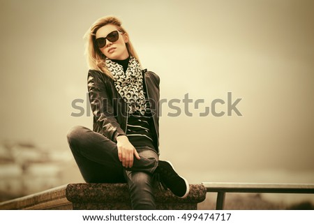 Happy young woman in leather jacket. Fashion model in sunglasses outdoor
