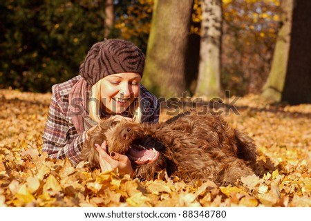 Happy Young Woman laying on autumn leaves with Dog