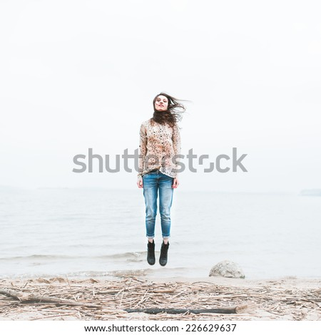 happy young woman on a coast on a windy day
