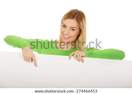 Happy young woman pointing on empty banner.