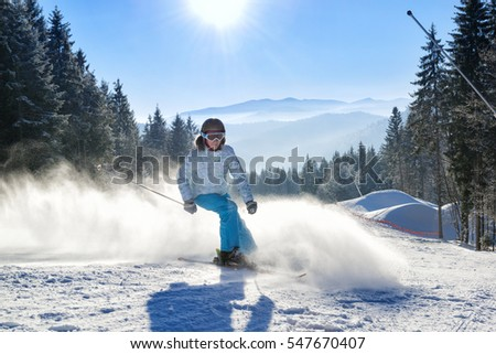 Happy young woman skiing on a winter resort slope with beautiful mountains on the background