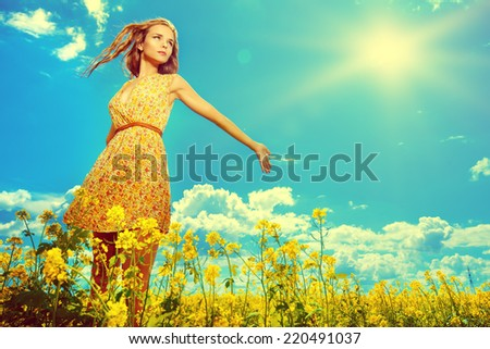 Happy young woman standing in a field of blooming yellow flowers. Summer.