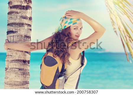 Happy young woman standing with backpack on coast sea and looking in camera. Freedom concept.