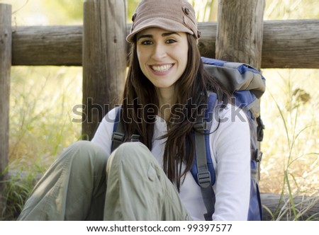 Happy young woman taking a break and relaxing on a hiking trip