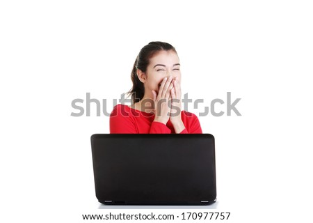 Happy young woman using her laptop at the desk, isolated on white.