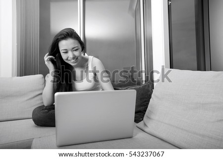 Happy young woman using laptop on sofa at home