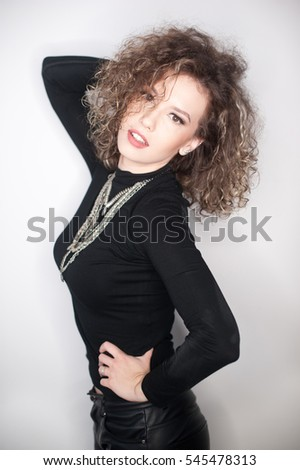 happy young woman with black blouse against white wall. Young woman with long curly hair posing in studio against white wall