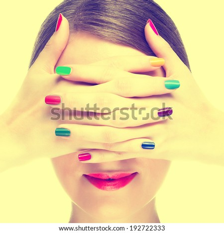 Happy young woman with colourful manicure. Toned image