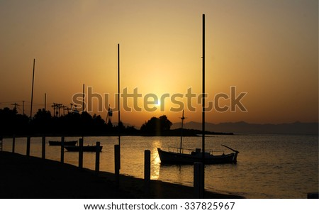 Harbor in the evening, silhouettes of luxury sailboat moored in the port, beautiful view on yachts, active summer vacation