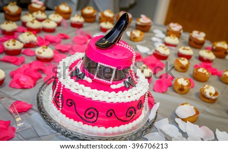 Hat Shaped Birthday Cake with a Pump Shoe as Crown: A lovely birthday cake shaped as a Church Hat and crowned with a single pump shoe.  Backdrop is a field of cupcakes.