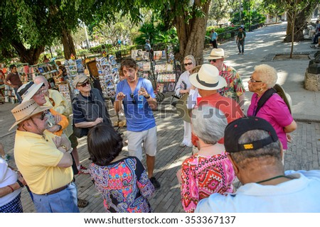 Havana, CUBA - March 19: A local tour guide with tourists in downtown Havana, Cuba