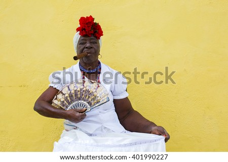 HAVANA, CUBA - MARCH 28, 2015: Cuban lady wears traditional clothing with cigar and fan while sitting on a chair in the old town of Havana, Cuba.