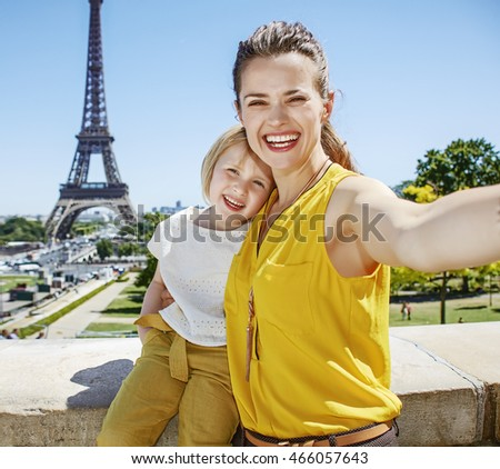Having fun time near the world famous landmark in Paris. smiling mother and child tourists taking selfie against Eiffel tower