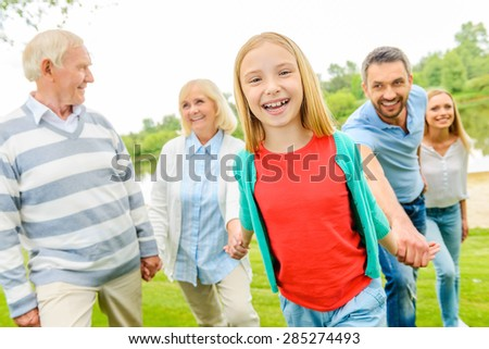 Having fun with family. Happy little girl enjoying time with her family while walking outdoors together