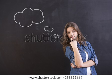 Having idea. Young woman is standing in front of blackboard and thinking about something.