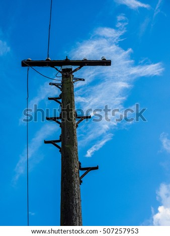 HDR Vintage wooden telegraph pole over the blue sky
