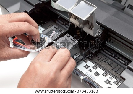 He is putting ink cartridges to a printer.